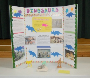 Science fair dinosaur display on poster board.