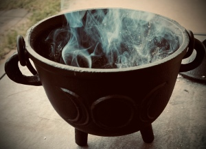 small iron cauldron with smoke coming from it.